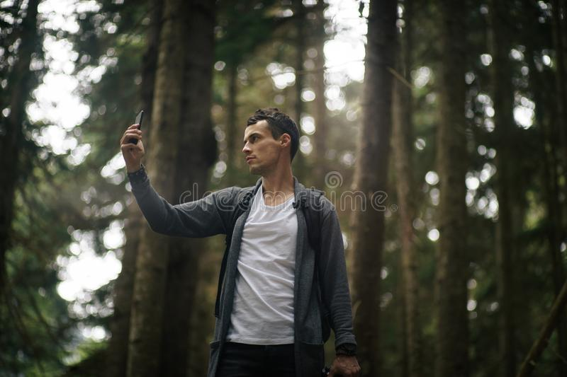 Self-confident man does selfie by the phone in the forest. Alone on the nature. Traveler lifestyle. royalty free stock image