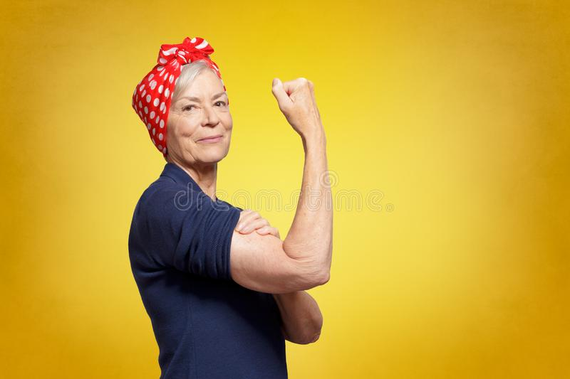 Self-confident senior woman rosie riveter. Senior rosie riveter concept: self-confident elderly woman with clenched fist rolling up her sleeve, copy space stock images
