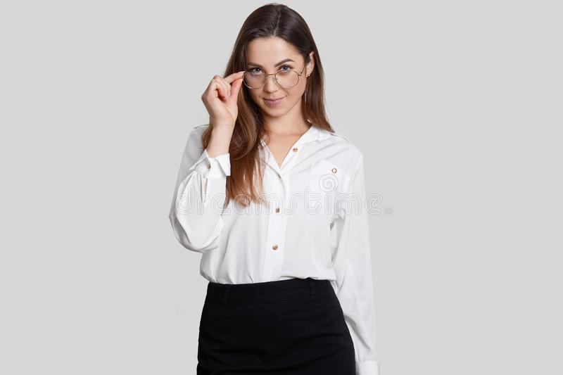 Self confident teacher wears round glasses, formal clothes, listens attentively answer of question, isolated over white background royalty free stock image