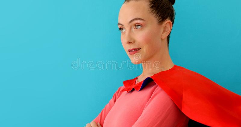 Self-confident woman in red cape, super hero royalty free stock images