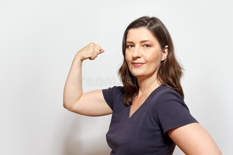 Woman flexing biceps muscles assertiveness. Middle aged woman flexing her biceps muscles, showing self-confidence and pride, symbol for girl or women power stock photography