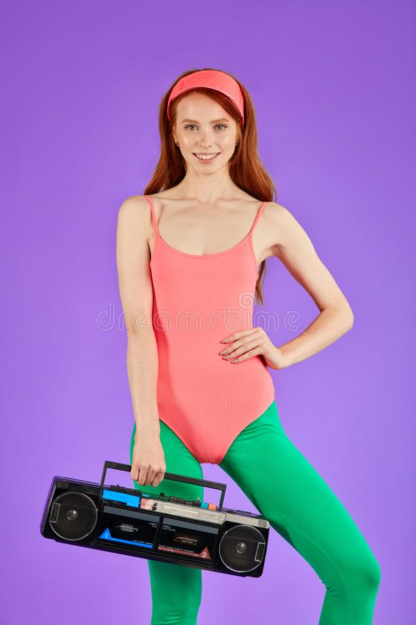 Young female fitness trainer stands during break between aerobics classes. Self-confident young female fitness trainer with red hair, glowing skin and cute stock images
