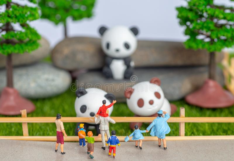 A self constructed miniature toys concept of people at the zoo - school kids and family watch pandas royalty free stock photo