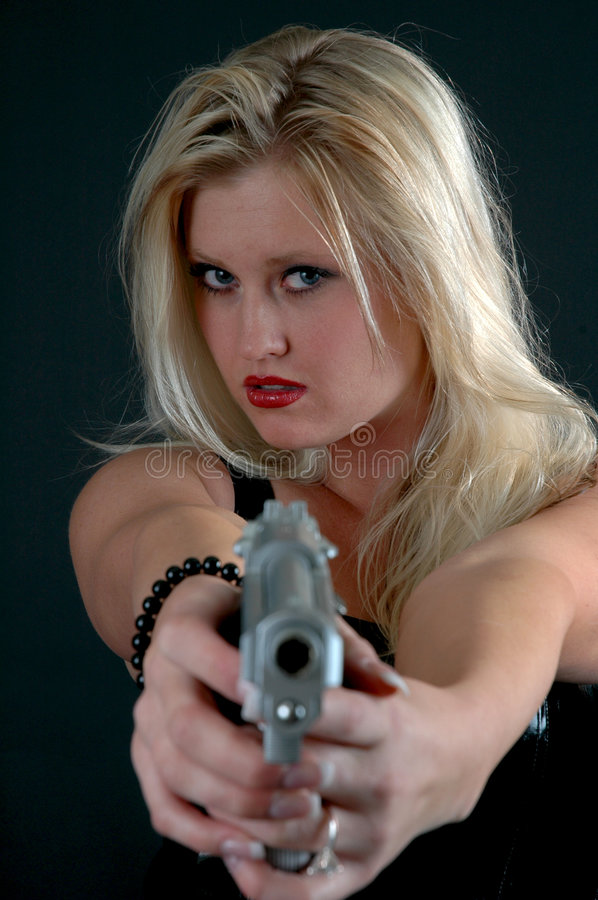 Self Defense. A beautiful woman pointing a gun royalty free stock images