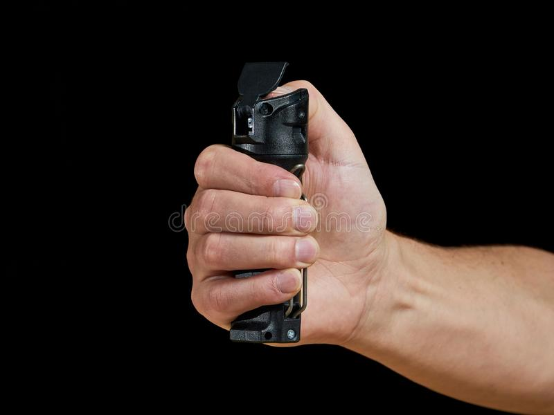 Self defense - aiming pepper spray. Male aiming pepper spray on black background stock images