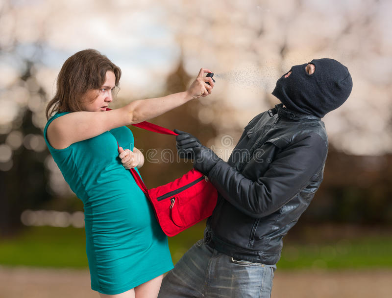 Self defense concept. Young woman is spraying with pepper spray on thief stock photo
