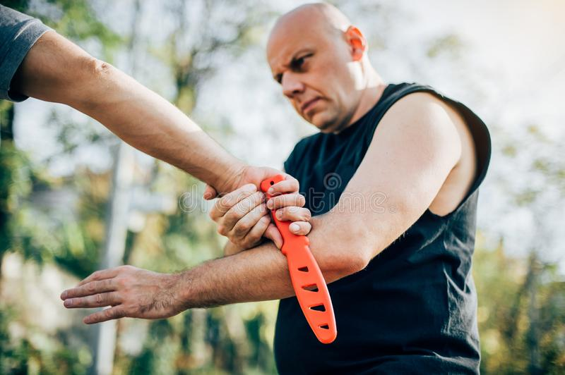 Self defense disarming technique against threat and knife attack royalty free stock image
