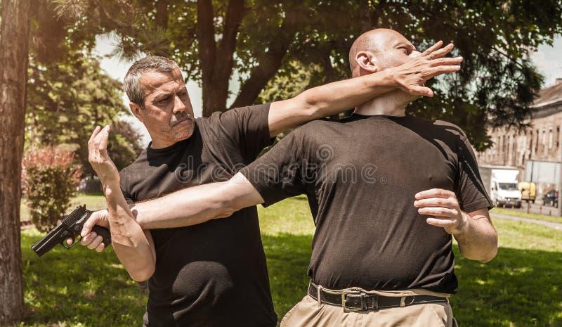 Self defense techniques against a gun. Kapap instructor demonstrates self defense techniques against a gun stock photography