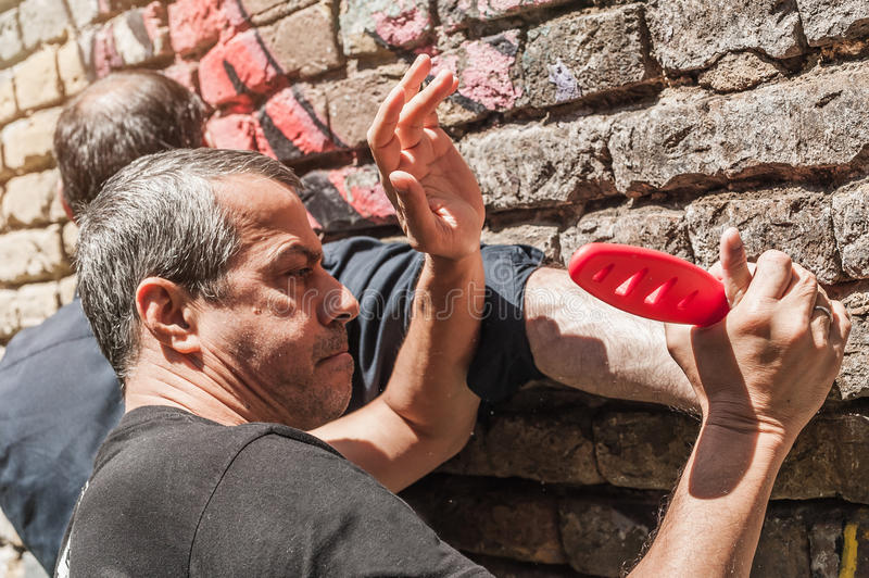 Self defense techniques against a knife attack. Kapap instructor demonstrates self defense techniques against a knife attack stock image
