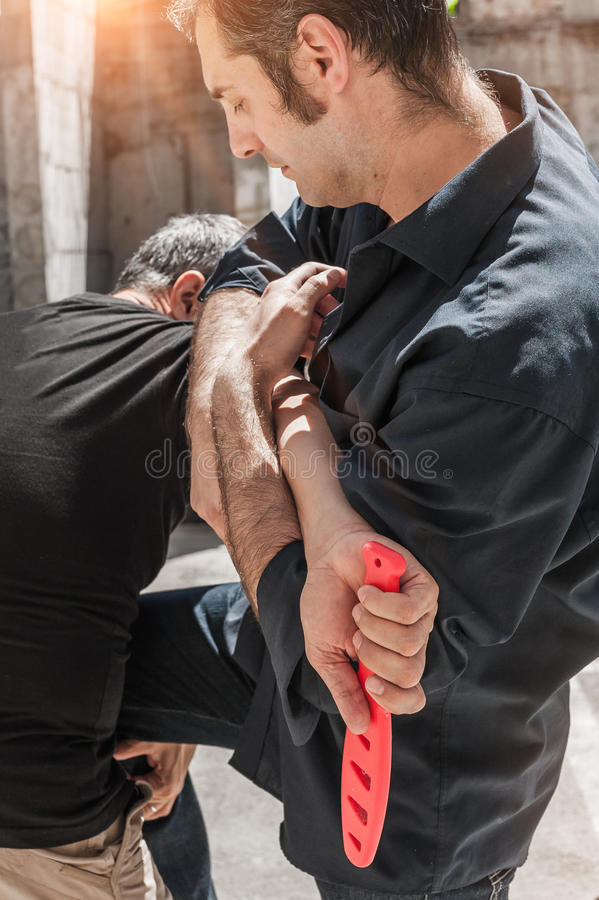 Self defense techniques against a knife attack. Kapap instructor demonstrates self defense techniques against a knife attack stock images