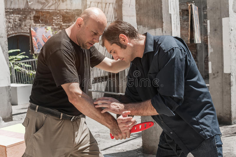 Self defense techniques against a knife attack. Kapap instructor demonstrates self defense techniques against a knife attack stock photos
