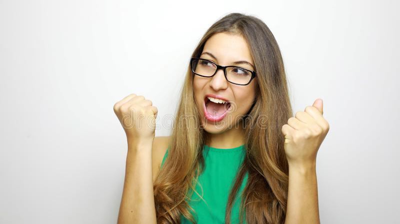 Self determined woman with glasses looking to the side with clenches fists and exclaims with triumph expression, cheers about royalty free stock photography