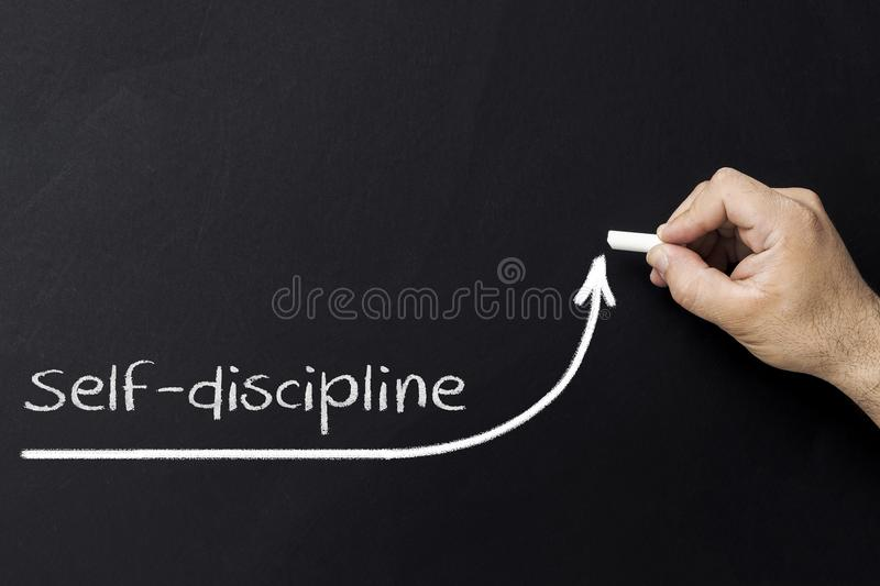 Self discipline concept. Hand with chalk drawing rising arrow. Discipline and self motivation. stock images