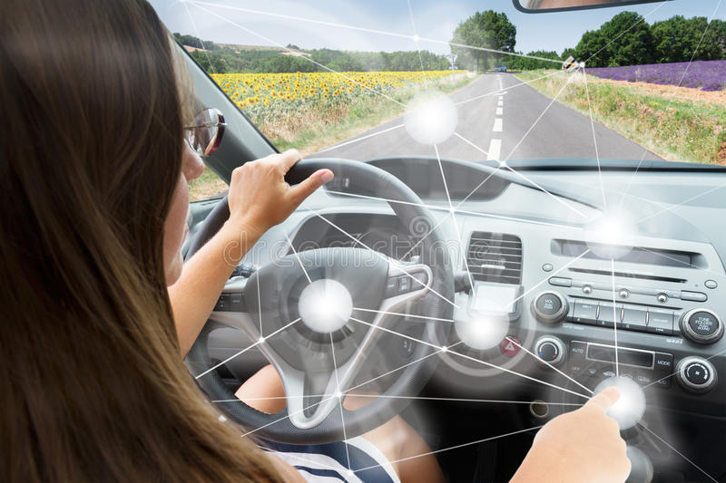 Self-driving car concept. Woman driving modern car royalty free stock images