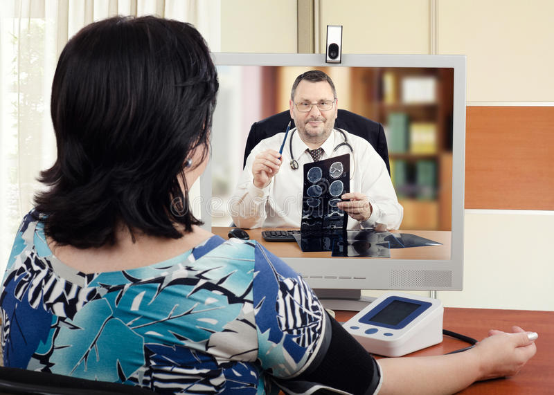 Self-employed cardiologist diagnoses online patient. Middle-aged cardiologist sits face to face with online female patient which measures her blood pressure royalty free stock photography