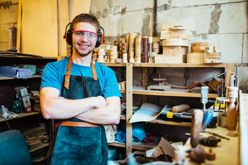Self-employed carpenter. Successful carpenter standing in his own workshop stock images