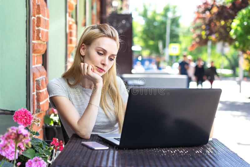 Self employed freelancer Caucasian woman working with her phone and laptop in a restaurant terrace in the street in a sunny day stock photo
