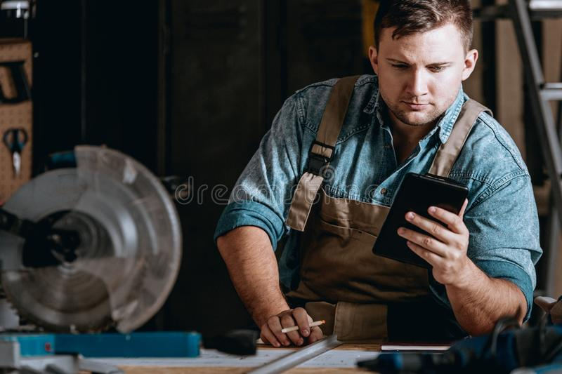 Self-employed machine constructor calculating costs. While working at manufacturing plant royalty free stock photos