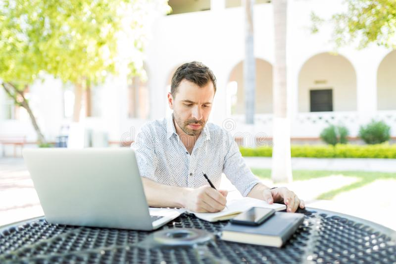 Self-Employed Man Preparing Schedule In Garden royalty free stock image