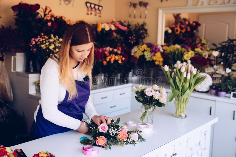 Self-employed young woman owner of florist shop arranging bouquet of roses. Wearing blue apron. Small business concept stock photos