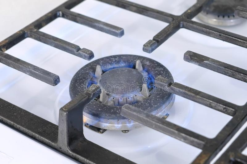 Self-igniting big gas berner turning on the cooktop gas sove. Gas stove with lattice. Close-up view stock photo