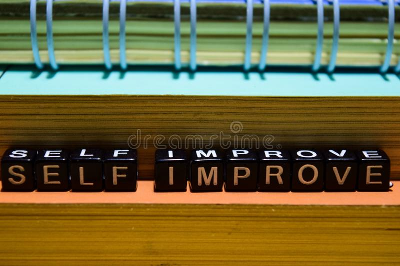 Self improve on wooden blocks. Education and business concept. On wooden background stock images