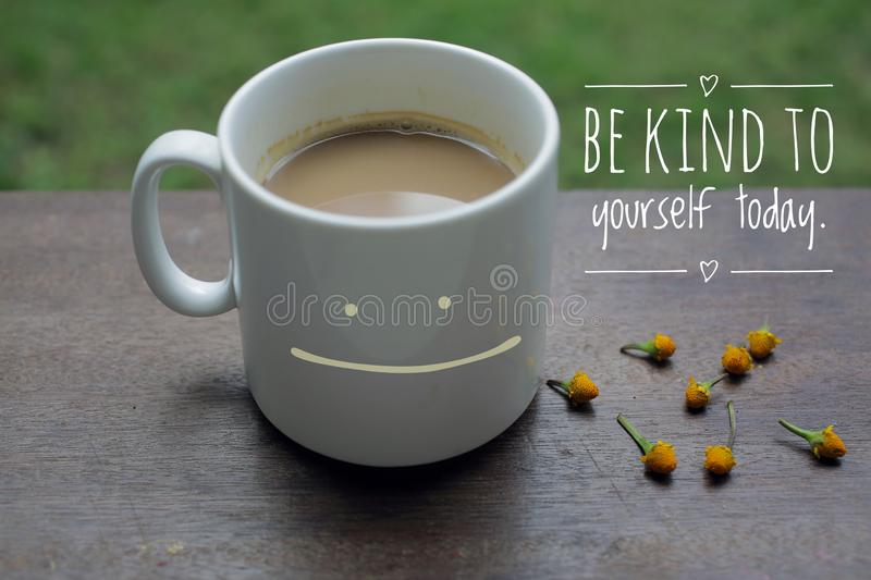 Self Inspirational motivational quote - Be kind to yourself. With smiling mug of white coffee on wooden table and little flowers. Arrangement. Morning coffee royalty free stock photo