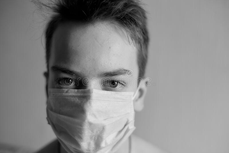 Self-isolation and quarantine, portrait of a teenage boy in a medical mask, protection from viruses and diseases.  stock image