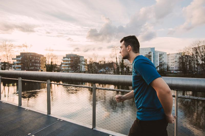 Self overcome concept. Young athletic man prepare for a sprint run practicing sport outdoors. Self overcome concept, conquering obstacles and win. Healthy stock photography