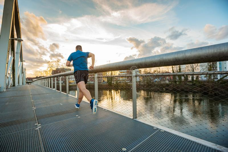 Self overcome. Young athletic man practicing sport outdoors, running fast along bridge over the sunset sky background. Self overcome conquering obstacles and win royalty free stock photos