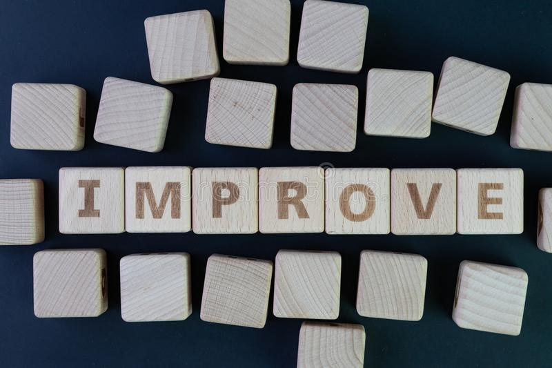Self or personal improvement concept by cube wooden block with a. Lphabet building the word IMPROVE at the center on dark blackboard background royalty free stock photos