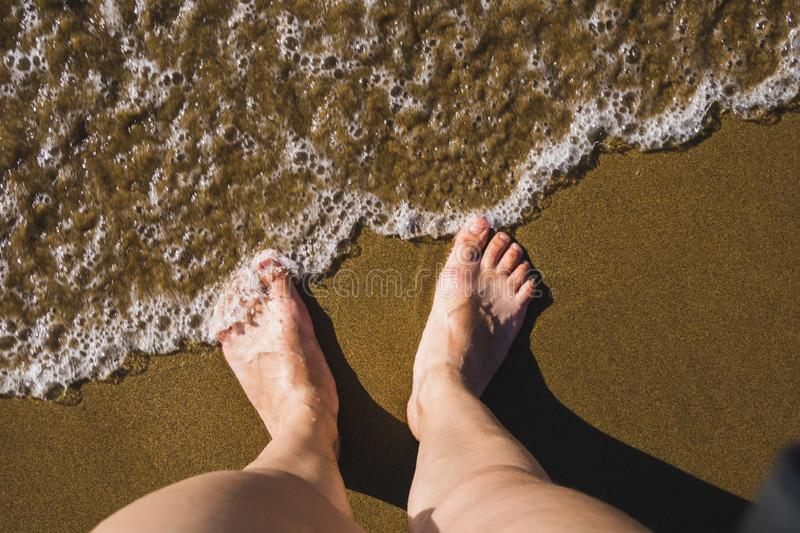 Self photo of the feet on the sand of a beach, waves coming towards the feet stock photos