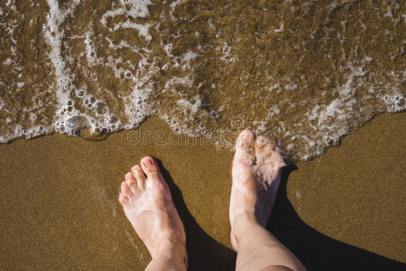 Self photo of the legs on the sand of a beach, waves touching the feet royalty free stock images