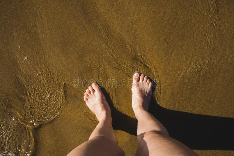Self photo of the feet on the sand of a beach, waves coming towards the feet royalty free stock photos