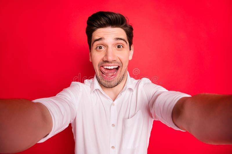 Self photo of fooling man playing camera grimacing in front of it while isolated with red background. Self photo of fooling man playing, camera grimacing in stock photos