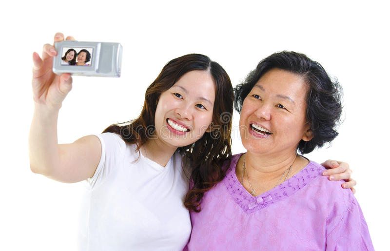 Self photographing. Asian girl and senior mother self photographing, isolated on white royalty free stock photography