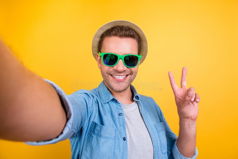 Self portrait of cheerful, bearded blogger in summer glasses, jeans shirt shooting selfie, showing peace symbol with two fingers. To the camera, making video royalty free stock photo