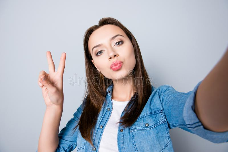 Self-portrait of confident brunette cute girl blowing kiss to t royalty free stock photo