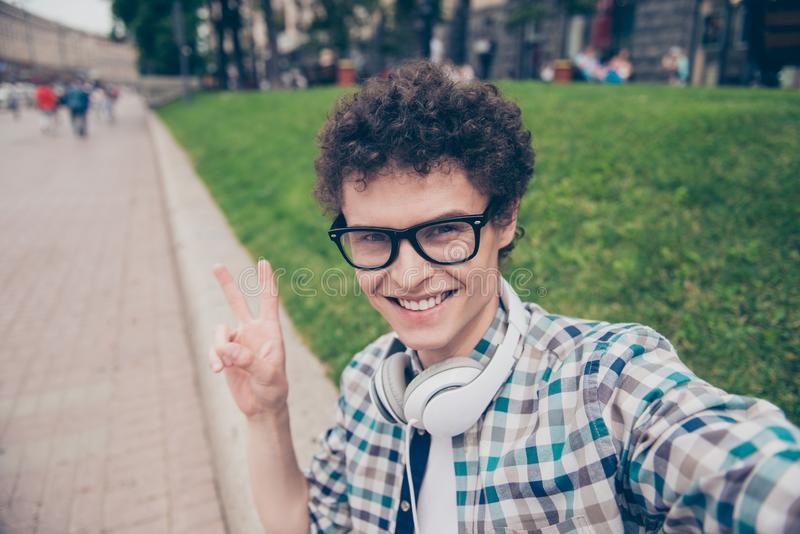 Self-portrait of curly haired cute attractive foolish smiling fu. Nky handsome guy wearing casual shirt and glasses outside making self photo, showing v-sign stock photography