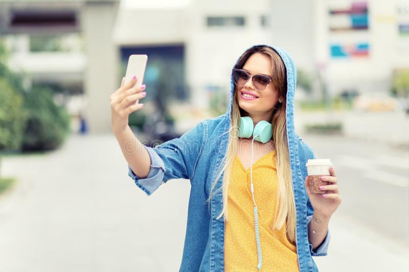 Self portrait of happy beautiful modern fashionable young woman drinking coffee on city street royalty free stock photography