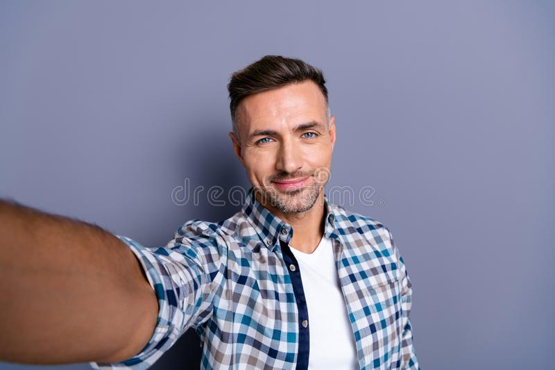 Self-portrait of his he nice-looking attractive well-groomed cheerful calm bearded grey-haired guy wearing checked shirt royalty free stock images