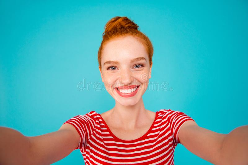 Self-portrait of nice stylish adorable attractive magnificent pr. Etty ecstatic cheerful red-haired girl with bun, isolated on bright vivid blue background royalty free stock photography