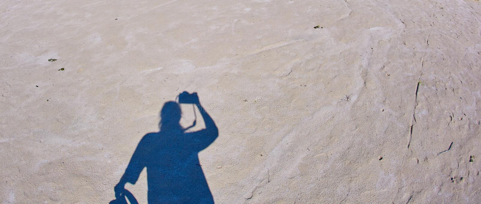 A self-portrait of a photographer with a camera in his hands casts a shadow on the sandy ground with a silhouette.  royalty free stock photography