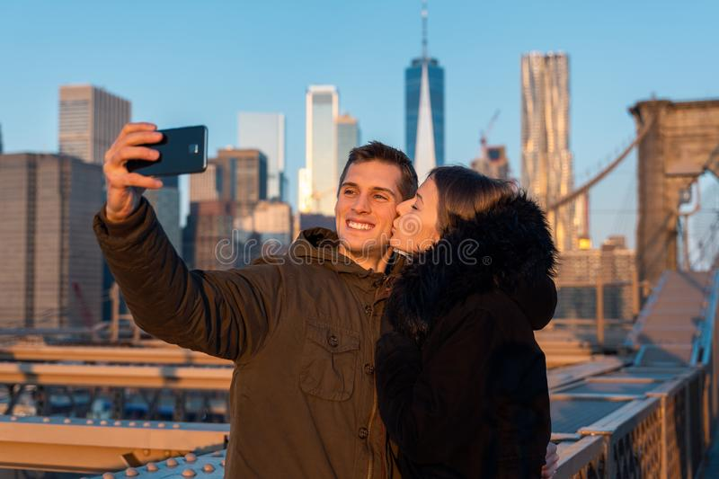 Couple taking a selfie on the brooklyn bridge in Manhattan, new York during sunset stock image