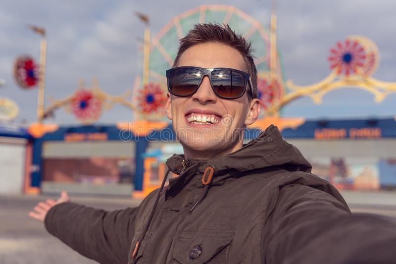 Man taking a selfie in coney island. Luna park as background stock photos