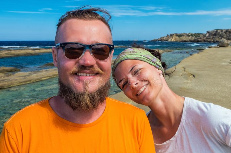 Self portrait of smiling couple tourists on vacations looking streight into camera with blue Mediterranean sea on royalty free stock image
