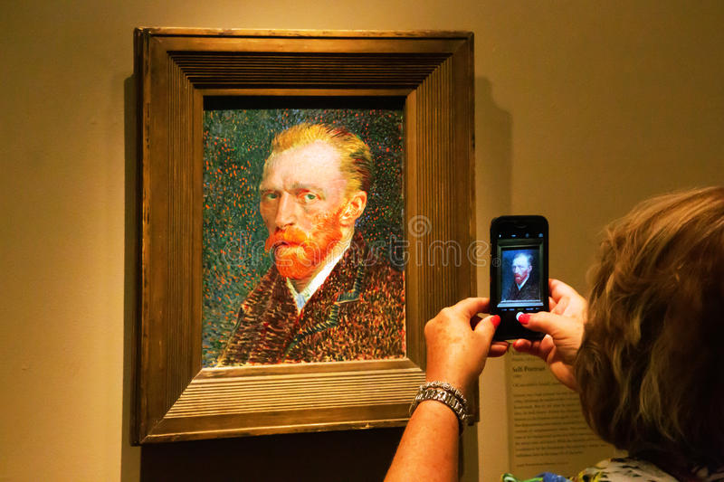 Self-portrait of Van Gogh in Art Institute of Chicago. Self-portrait by Vincent van Gogh in Art Institute of Chicago. A visitor is taking a picture with the royalty free stock images