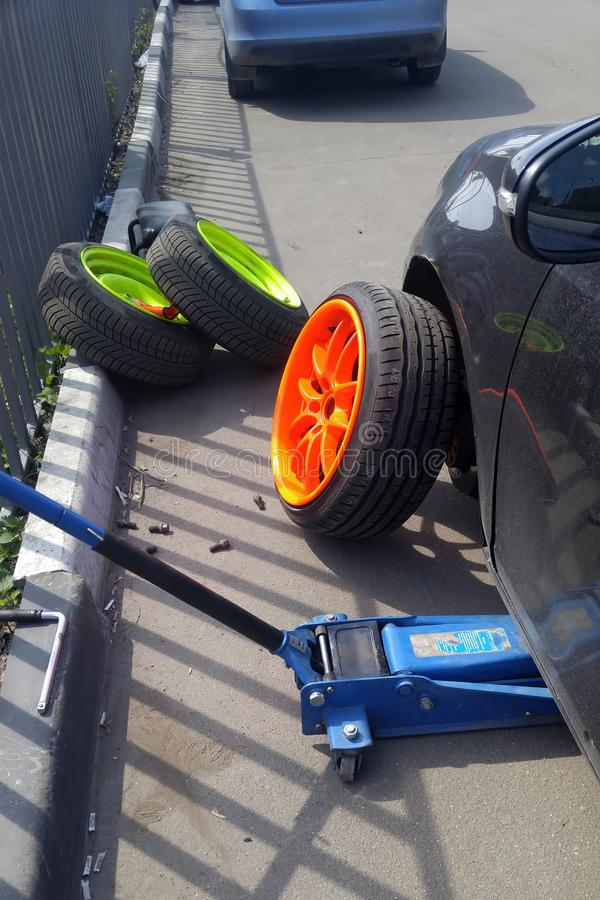 Self replacement wheels. Tire DIY. Replacing the wheels of lemon-neon color with orange-colored wheels. Jacki stock images