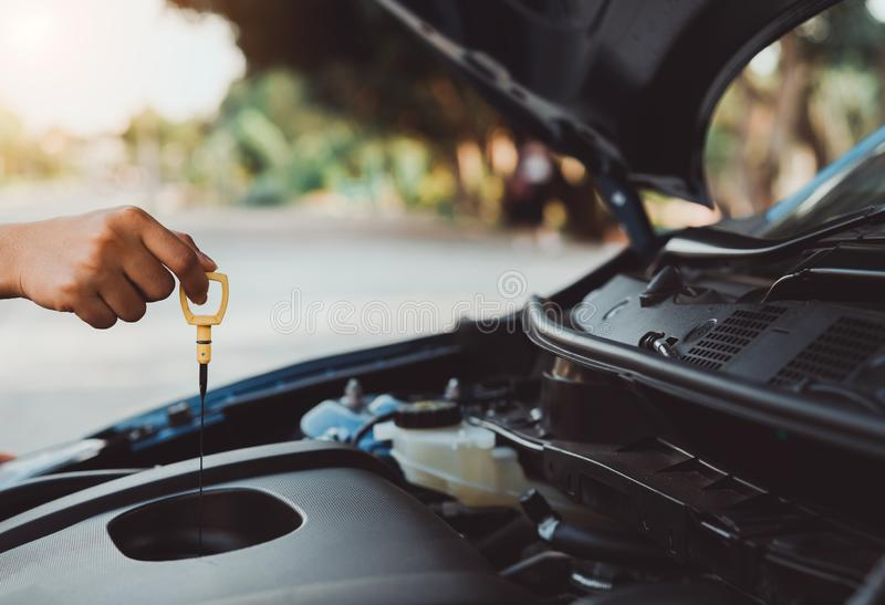 Self service hand use dipstick checking engine oil level. Car vehicle,professional woman maintenance and repair before travel transportation for safety driving royalty free stock photos
