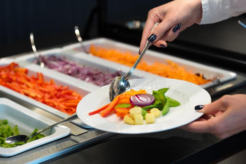 Self service at a salad buffet, catering business vegan food. Self service at a salad buffet, catering business, vegetable plate, vegan meal royalty free stock photos